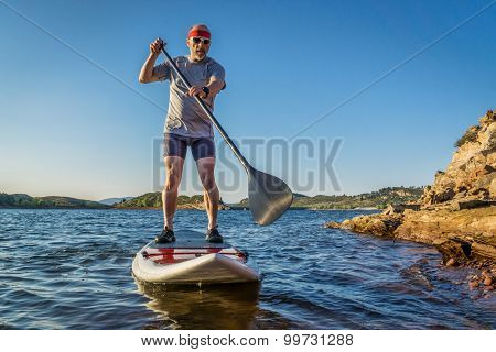 senior male paddler enjoying stand up paddling on a sunny summer day - Horsetooth Reservoir, Fort Collins, Colorado