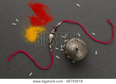 An elegant Rakhi thread on black background with haldi-kumkum and rice grains. View from top.