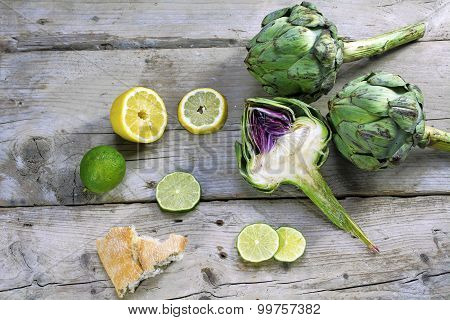 Artichokes Whole And Halved With Lemons, Limes And Bread On Weathered Wood