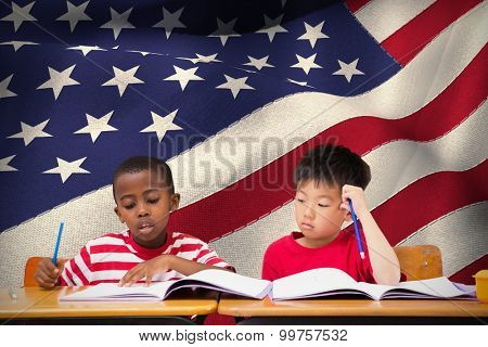 Cute pupils writing at desk in classroom against digitally generated american national flag poster