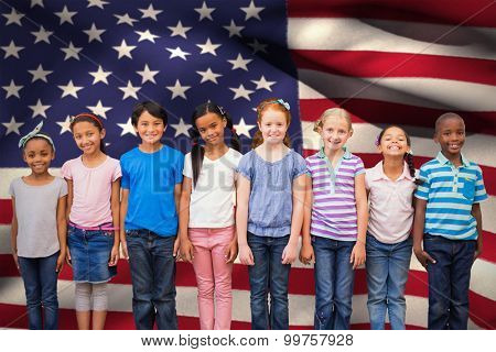 Cute pupils smiling at camera in classroom against digitally generated american national flag poster