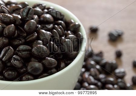 Cup full of coffee beans with wood table