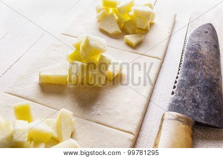 prepared apple turnovers on wooden table with knife