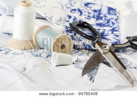 Thread in White and blue, fabric and scissor
