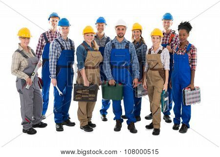Portrait Of Confident Carpenters Carrying Toolboxes