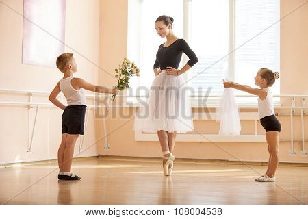 At ballet dancing class: young boy and girl giving flowers and veil to older student.