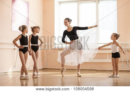 Young girl warming up and talking to younger classmates.