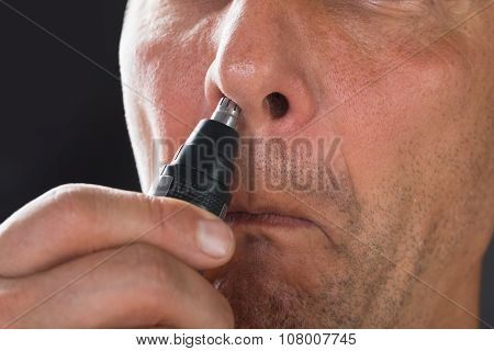 Man Removing Hair From His Nose With Trimmer