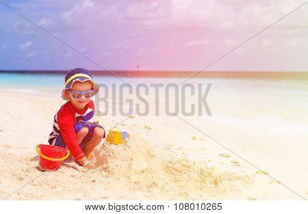 little boy building sandcastle on tropical beach