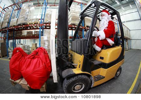 Santa Claus as a forklift operator at work in warehouse