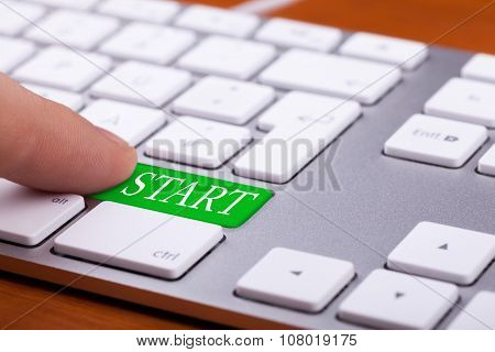 Finger Pressing Green Start Button On Keyboard