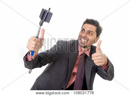 Young Attractive Businessman In Suit And Tie Taking Selfie Photo With Mobile Phone Camera And Stick