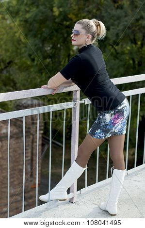 The Sexy Woman In White Boots And A Miniskirt On The Bridge Looking Afar