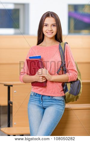 Attractive young girl holding her textbooks.