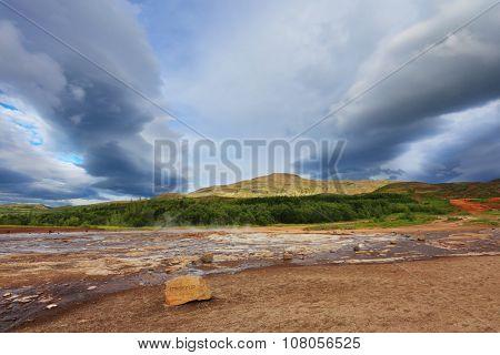 Summer Iceland. Fumaroles Geyser Strokkur. Water vapor from the crater geyser under bizarre clouds