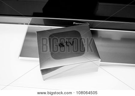 PARIS FRANCE - NOV 10 2015: New Apple TV media streaming player microconsole by Apple Computers - box near Panasonic TV. It has new touch remote swipe-to-select with integrated Siri and motion sensor