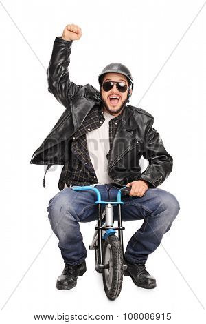 Vertical shot of an excited male motorcyclist riding a tiny bicycle and gesturing happiness isolated on white background