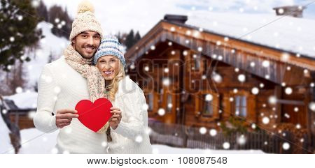 love, valentines day, couple, christmas and people concept - smiling man and woman in winter hats and scarf holding red paper heart shape over wooden country house and snow background