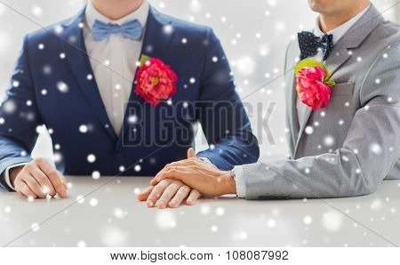 people, homosexuality, same-sex marriage and love concept - close up of happy married male gay couple in suits with buttonholes and bow-ties holding hands on wedding over snow effect