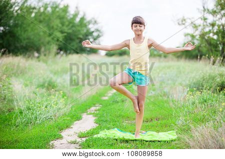 Little girl standing in tree yoga position