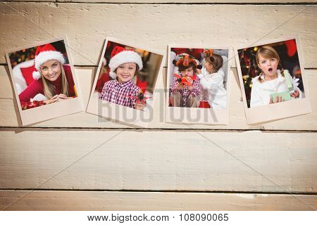Instant photos on wooden floor against shocked little girl opening a gift