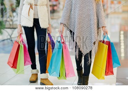 Modern shoppers with paperbags going in the mall