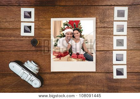 Happy couple celebrating Christmas at home against view of an old camera with photos slides