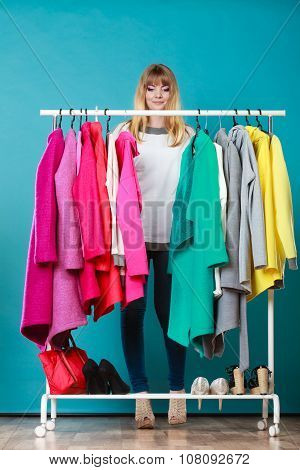 Pretty woman choosing clothes to wear in wardrobe. Attractive young girl customer shopping in mall shop. Fashion clothing sale concept. poster