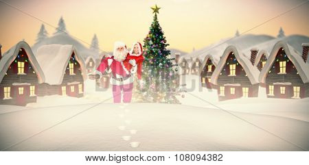 Santa and Mrs Claus smiling at camera against cute christmas village with tree