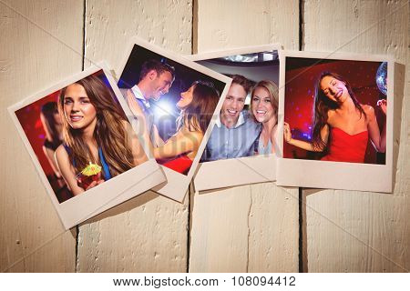 Instant photos on wooden floor against pretty brunette dancing and smiling