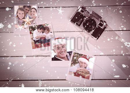 Family Christmas portrait against instant photos on wooden floor