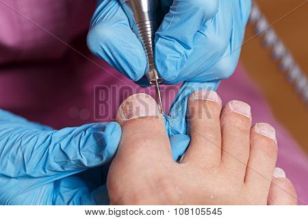 Master pedicure shapes the nails and cuticles closeup. Hardware manicure. Concept body care. poster