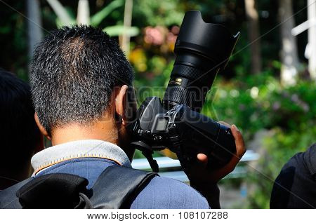 Group of Asian professional photographer on outdoor duty in public