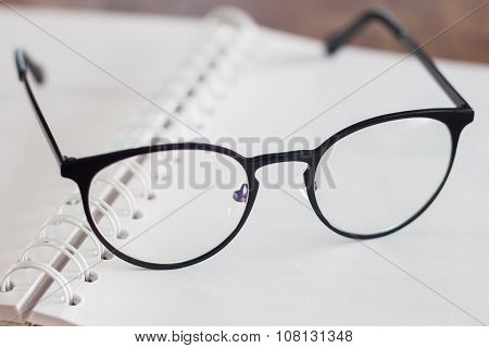 Eyeglasses On Opened Spiral Notebook