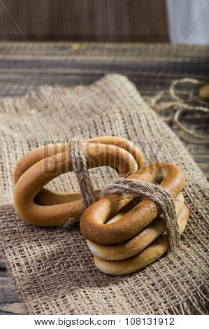 Photo closeup groups of delicious hard oval cracknels bind with string in bunches in threes laying sackcloth coarse fabric on wooden table over rustic background vertical picture poster
