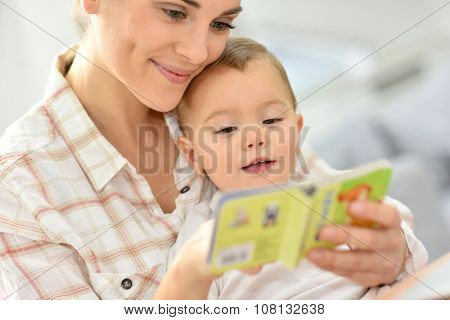 Sweet moment with mother reading book to baby