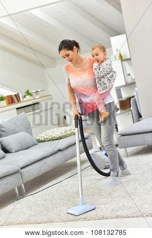 Mother vaccum cleaning floor with baby in arms