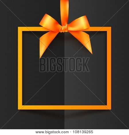 Orange gift box frame with silky bow and ribbon on black folded paper background