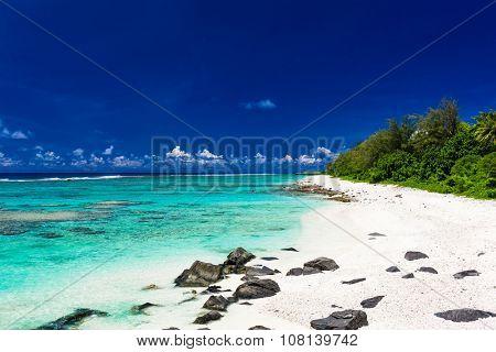 Amazing beach with white sand and black rocks on Rarotonga, Cook Islands