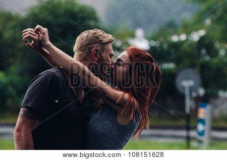 beautiful couple kissing in the rain