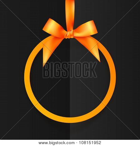 Orange round frame with silky bow and ribbon at black folded paper background