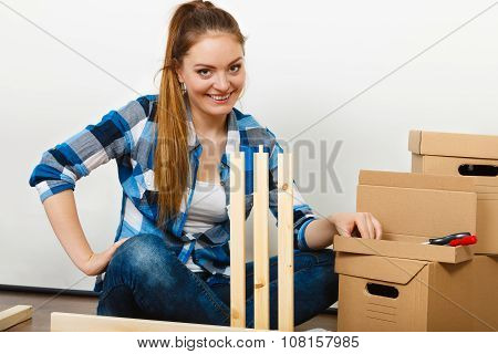Woman moving into new apartment house assembling furniture. Young girl arranging interior and unpacking boxes. poster