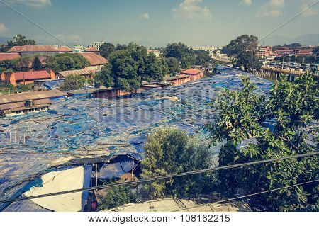 Local market covered with blue plastic sheets and tyres.