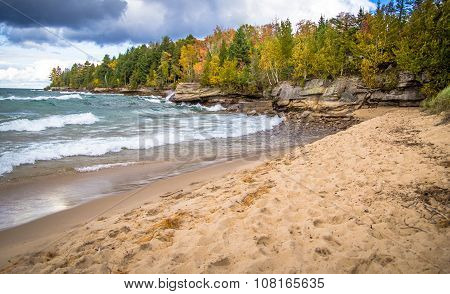 Sandy beach leads to a wind swept rocky coast with the colors of autumn decorating the Lake Superior coast in Christmas, Michigan. poster