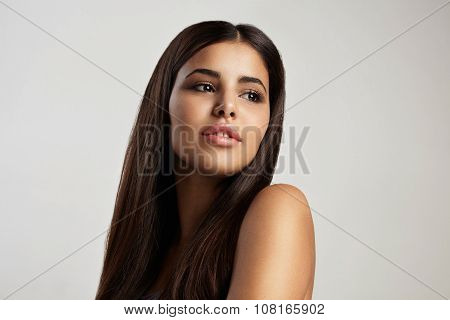 neutral makeup brunette latin woman watching aside poster