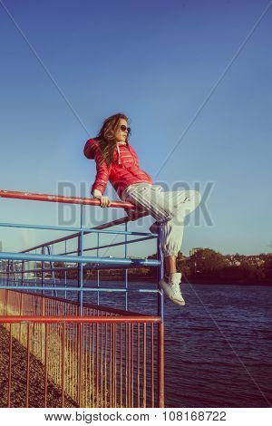 girl in sports red winter jacket sit on edge of  the metal fence looking in distance full body shot, sunny autumn day