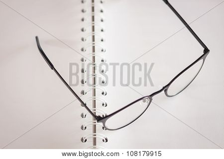 Eyeglasses On Opened Spiral Notebook