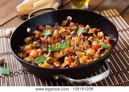 Italian Caponata with frying pan on a wooden background.