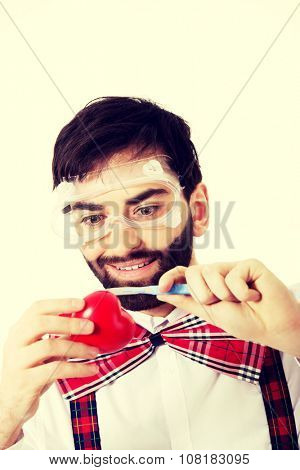 Determined man wearing suspenders cutting heart model with scalpel.. poster