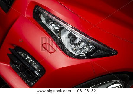 Predatory car headlight and hood of powerful sports car with matte red paint and wheel with silver disc poster